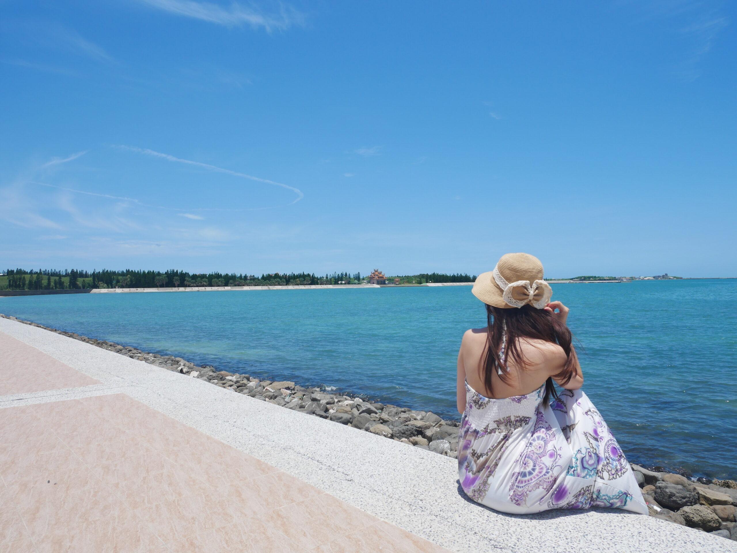 穿著洋裝戴著帽子女孩在澎湖講美海灘的自拍