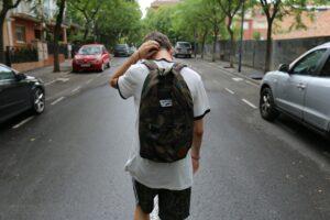一個背著背包摸著頭走在兩輛車中間不知所措的少年